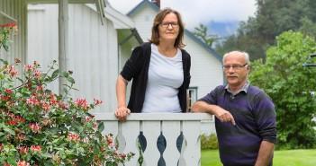 Olga og Geir Remmem ved inngangen til sin bolig – i enden av den 25 meter lange hovedbygningen. Foto: June Witzøe